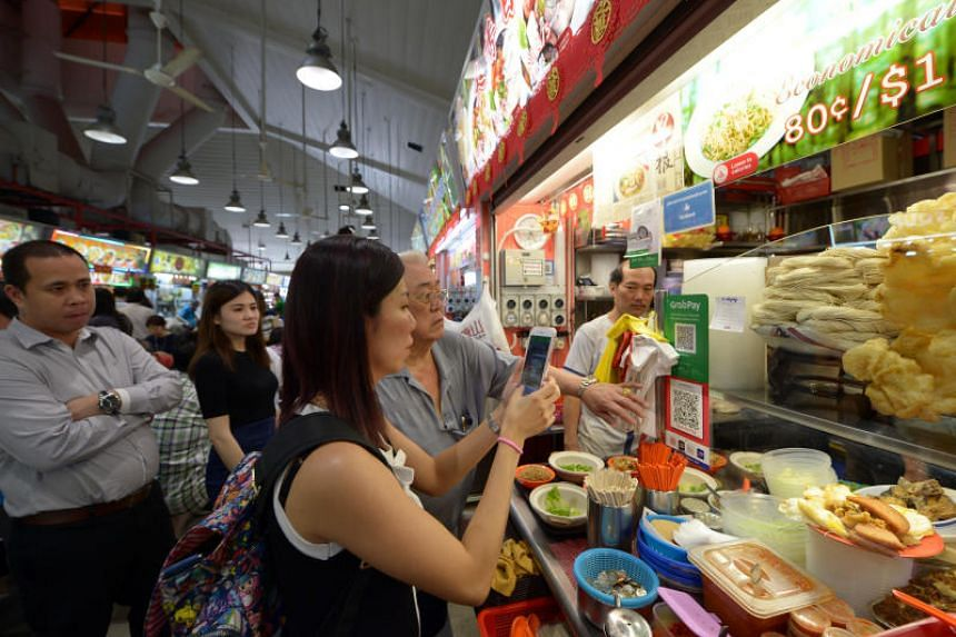 A customer pays for her lunch at the Tanjong Pagar Plaza Market and Food Centre using the QR code payment system on Feb 13, 2018.