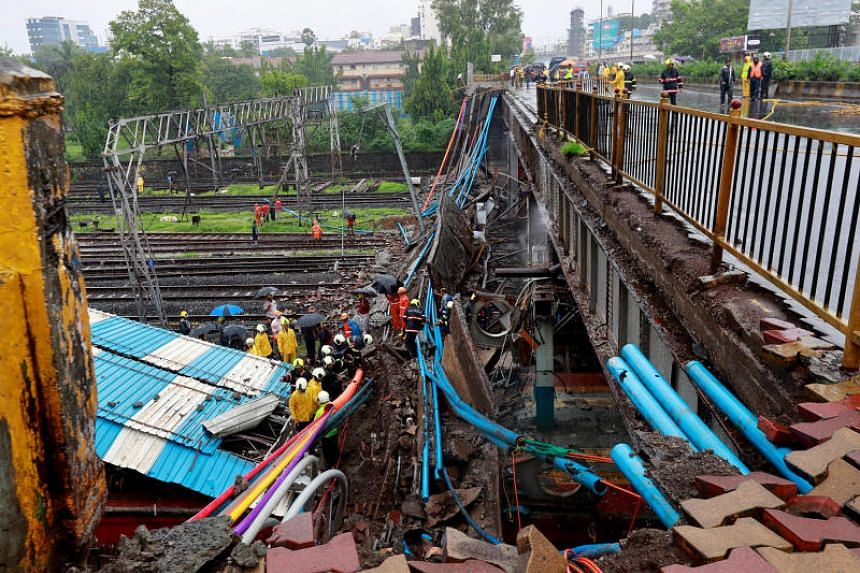 Rescue workers at the site of an overhead bridge that collapsed over the railway tracks after heavy rains in Mumbai, on July 3, 2018.