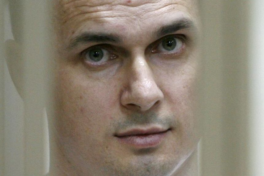 Ukrainian film director Oleg Sentsov looks on inside a defendants' cage during a hearing at a military court in the city of Rostov-on-Don on July 22, 2015.