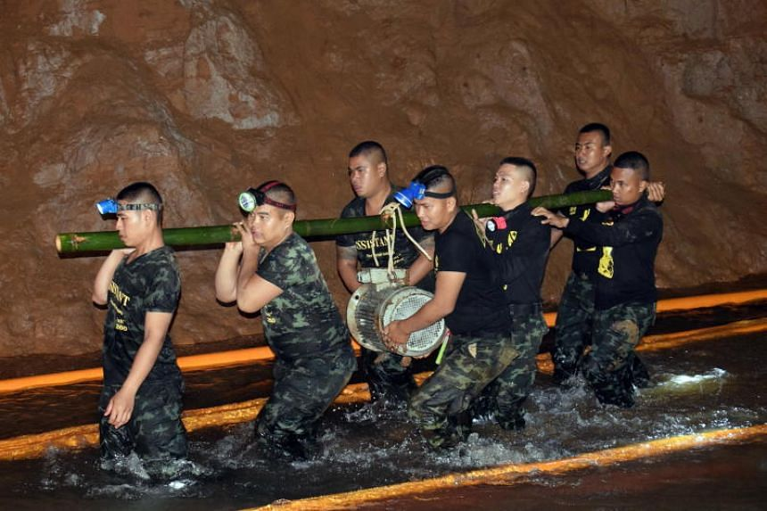 Thai soldiers carrying equipment inside the flooded cave complex during a rescue operation for a missing youth football team and their coach at Tham Luang cave in Khun Nam Nang Non Forest Park, Chiang Rai province, Thailand, in an undated handout pho