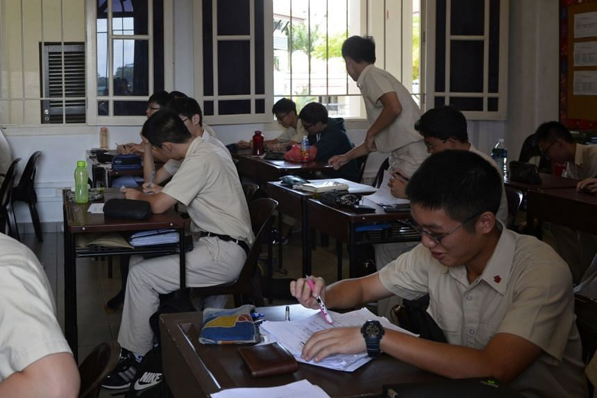Secondary school students attending a class. Singaporean children returning from overseas who wish to join an educational institution are required to take tests to determine the schools they are eligible for.
