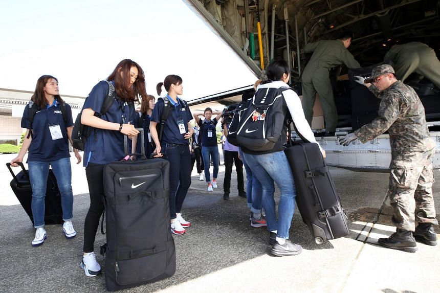 Members of South Korea's basketball delegation load their luggage on a military plane that will take them to Pyongyang, at an airport in Seongnam, South Korea, on July 3, 2018.