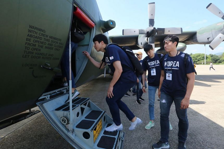 South Korean men's basketball team players board a plane to leave for Pyongyang, North Korea, on July 3, 2018.
