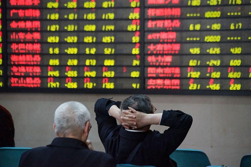 Investors look at an electronic board showing stock information at a brokerage house in Nanjing, Jiangsu province, China.