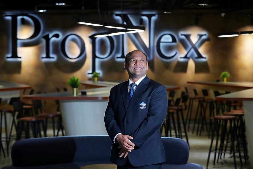 Mr Ismail Gafoor, CEO of PropNex, posing for a photo in front of the company's logo.