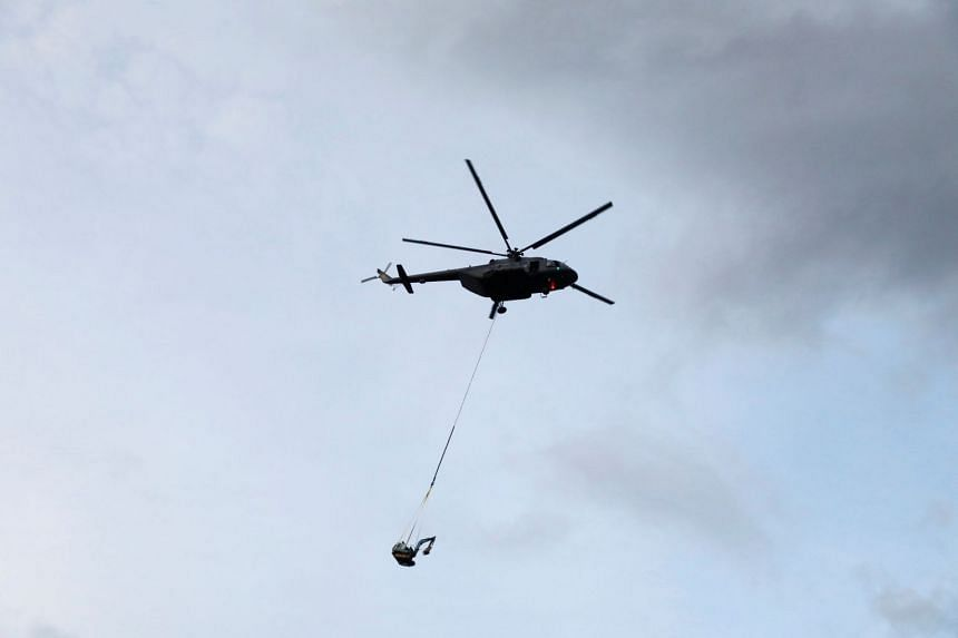 A helicopter transporting heavy machinery that will be used to make a new entrance at the top of Tham Luang cave complex, on July 1, 2018.