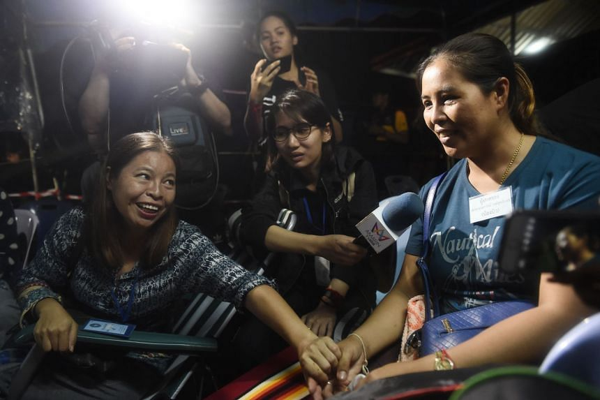 Relieved family members celebrating upon news that all members of children's football team and their coach were alive in the cave at Khun Nam Nang Non Forest Park, on July 2, 2018.