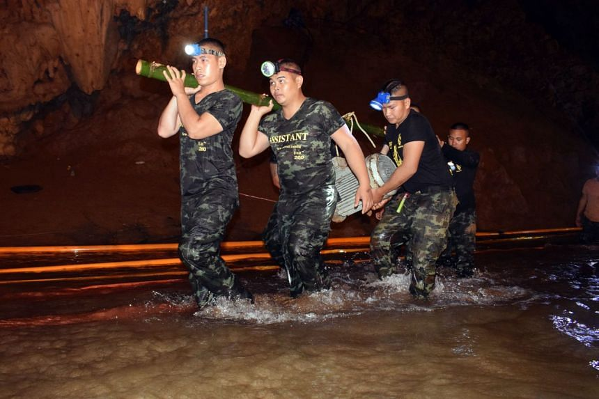 Thai soldiers carrying equipment inside the flooded cave complex as the rescue operation for a missing youth soccer team and their coach at Tham Luang cave continues in the Chiang Rai province, Thailand.