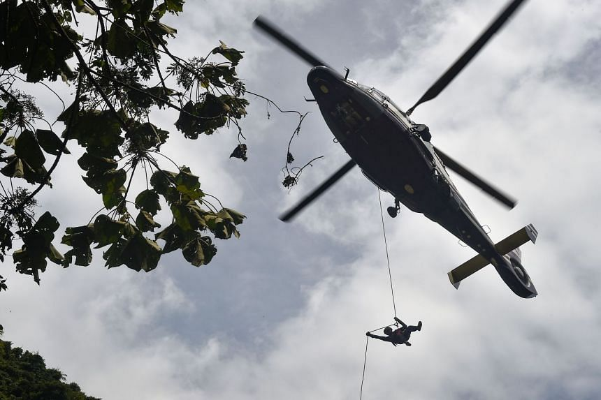 A Thai Airforce worker dropping into the forest by helicopter as the rescue operation continues, on June 30, 2018.