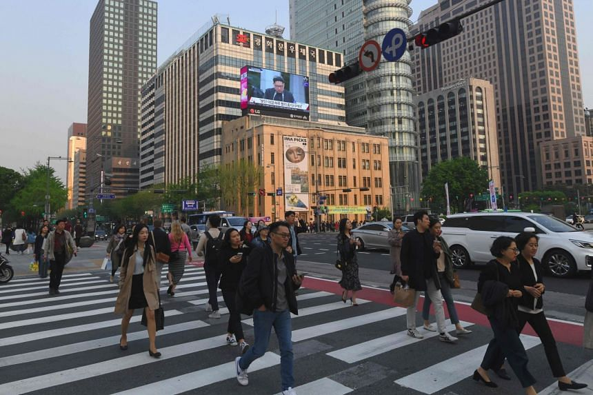 Pedestrians crossing the road in Seoul, South Korea. Many are cautiously optimistic over the possibility of having better work-life balance as the 52-hour workweek kicks off.