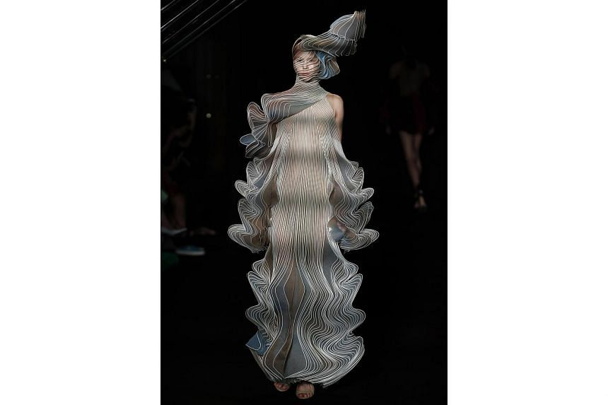 Dutch designer Iris van Herpen pushes boundaries with futuristic designs, including a pleated dress that blossoms into a headdress (above).