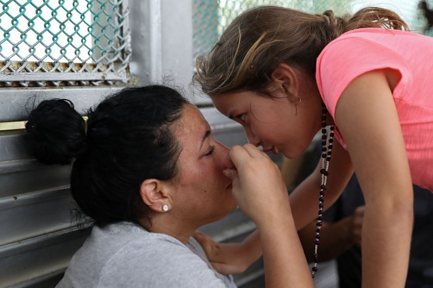 A Cuban mother seeking asylum is comforted by her daughter while waiting on the Mexican side of the Brownsville-Matamoros International Bridge after being denied entry by US Customs and Border Protection officers near Brownsville, Texas, US.