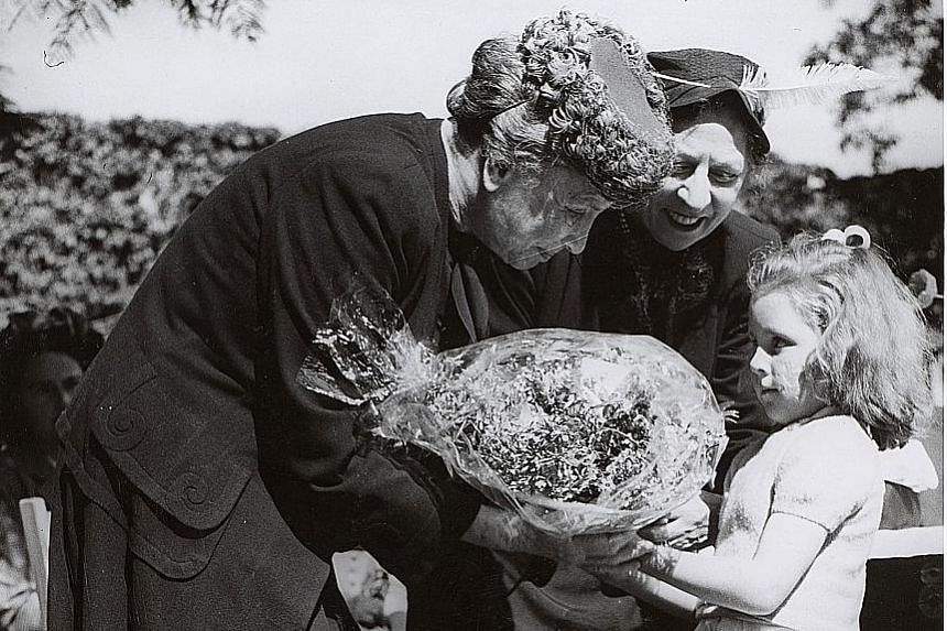 A child presenting a bouquet to Helen Keller, who visited more than 39 countries in her lifetime and did advocacy work.
