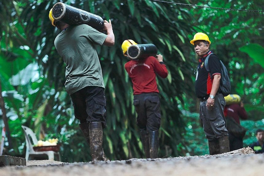 Thai rescue workers carrying oxygen tanks for the rescue operation at Tham Luang cave. The rescue team is also said to be bringing supplies and food into the cave.