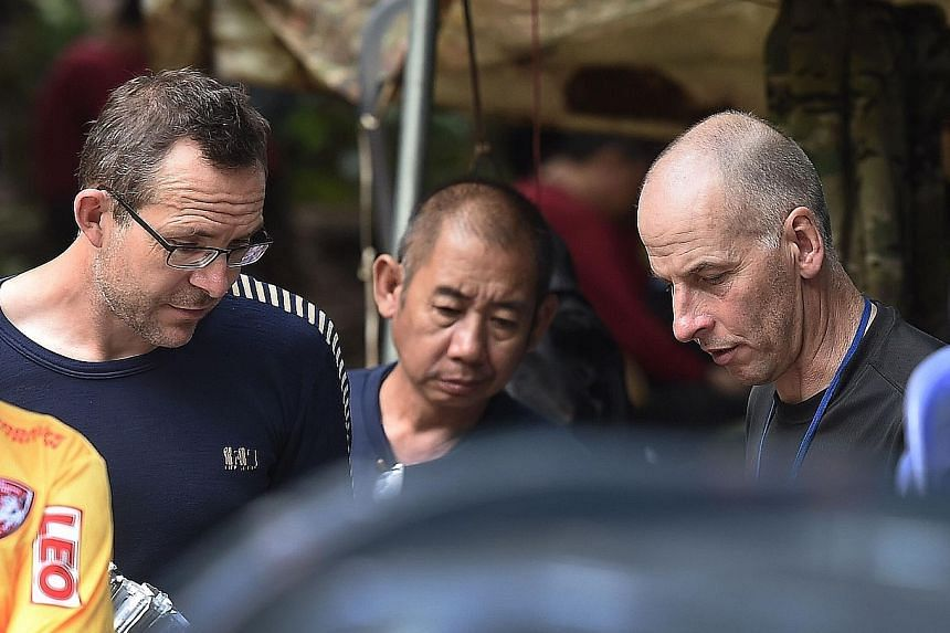 British divers John Volanthen (at left) and Richard Stanton, seen here with a Thai rescue team member at the Tham Luang cave area in Chiang Rai Province yesterday, after finding the boys and their coach alive in the cave.
