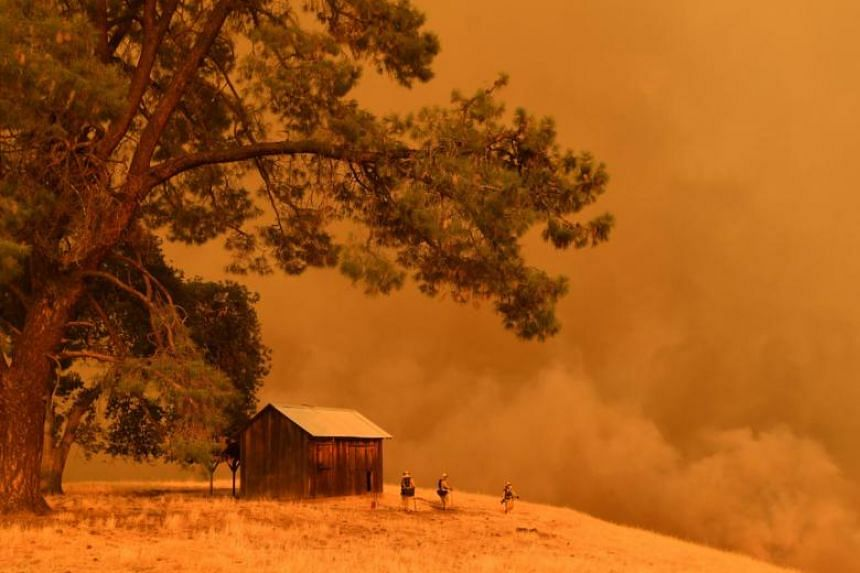 Firefighters watch as flames from the County Fire climb a hillside in Guinda, California, on July 1, 2018.