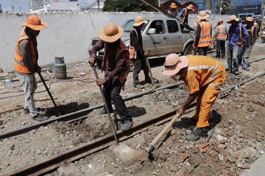 Cambodian labourers work at a railway near a train station in Phnom Penh, Cambodia, on July 4, 2018.
