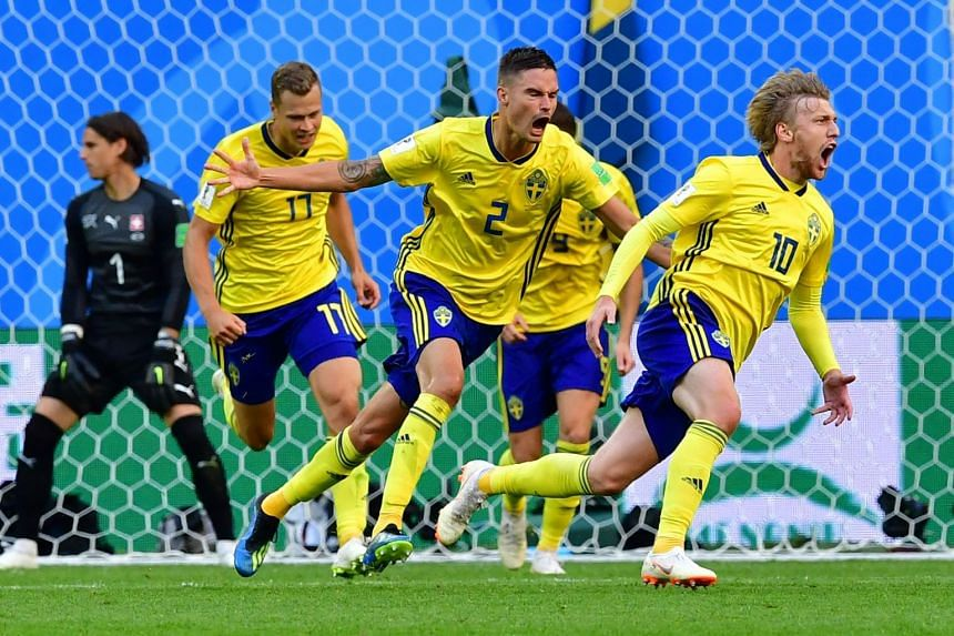 Sweden's midfielder Emil Forsberg (right) celebrates scoring during the Russia 2018 World Cup round of 16 football match between Sweden and Switzerland.