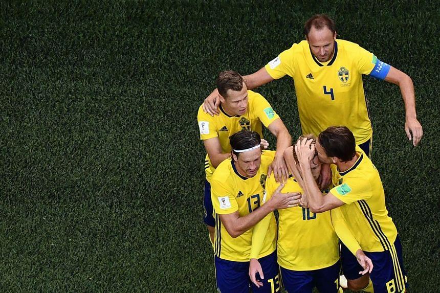 Sweden's midfielder Emil Forsberg (centre) celebrates with teammates after scoring.