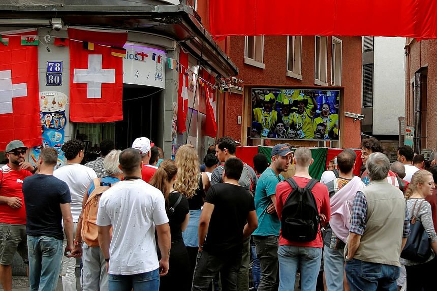 Fans watch the match at a public viewing event in front of a bar in Zurich, Switzerland, on July 3, 2018.