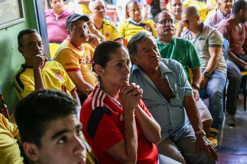 Fans of Colombia react while watching the World Cup 2018 round of 16 football match between Colombia and England at la Comuna 13 in Medellin, Colombia, on July 3, 2018.