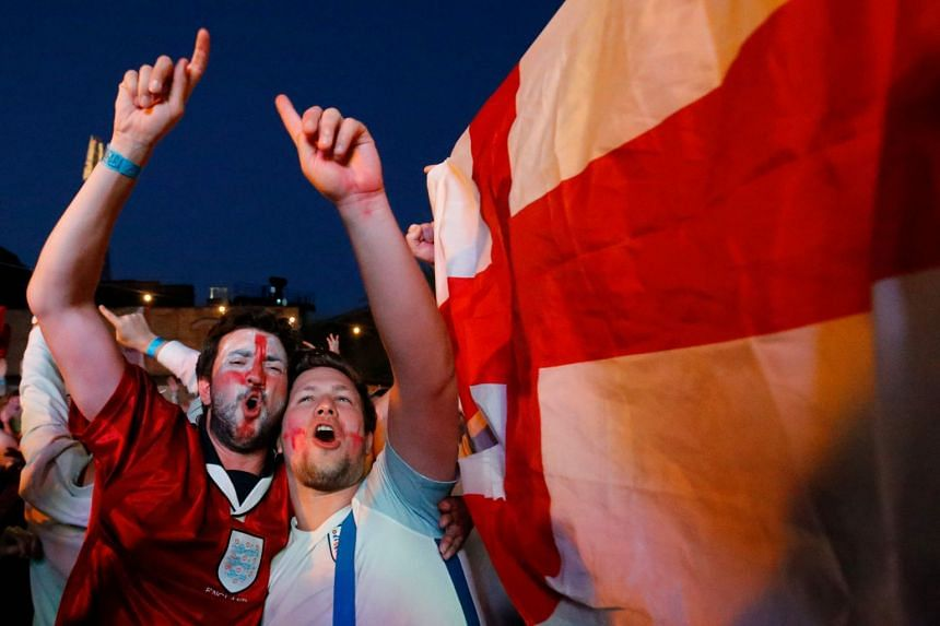 Fans celebrate after England won in the penalty shoot out as they watch the World Cup 2018 round of 16 football match between Colombia and England on a big screen in London, on July 3, 2018.