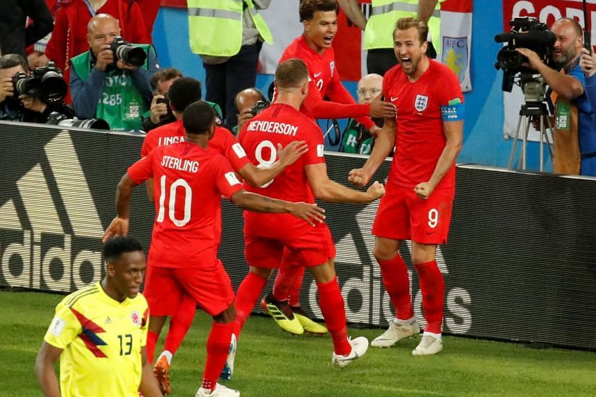 England's Harry Kane celebrates with his team mates after scoring a goal against Colombia, on July 4, 2018.