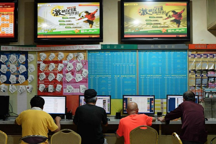 People checking for information about the 2018 Russia World Cup tournaments at a China Sports Lottery outlet in Shanghai, on July 2, 2018. Proceeds from Chinese gamblers have already outstripped the whole of the 2014 tournament in Brazil.