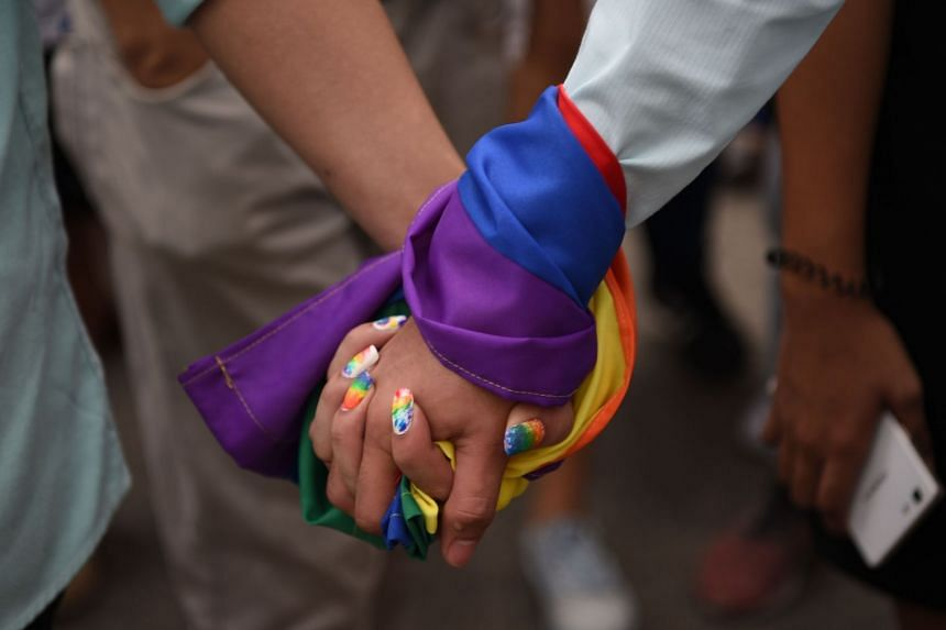 File photo showing a rainbow flag around the hands of a couple. Hong Kong's LGBT community's fight for legal rights has received support from multinational companies.