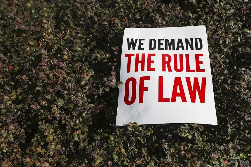 A placard from former Malaysian prime minister Najib Razak's supporters lies on bushes in front of the Kuala Lumpur High Court in Kuala Lumpur, Malaysia, on July 4, 2018.