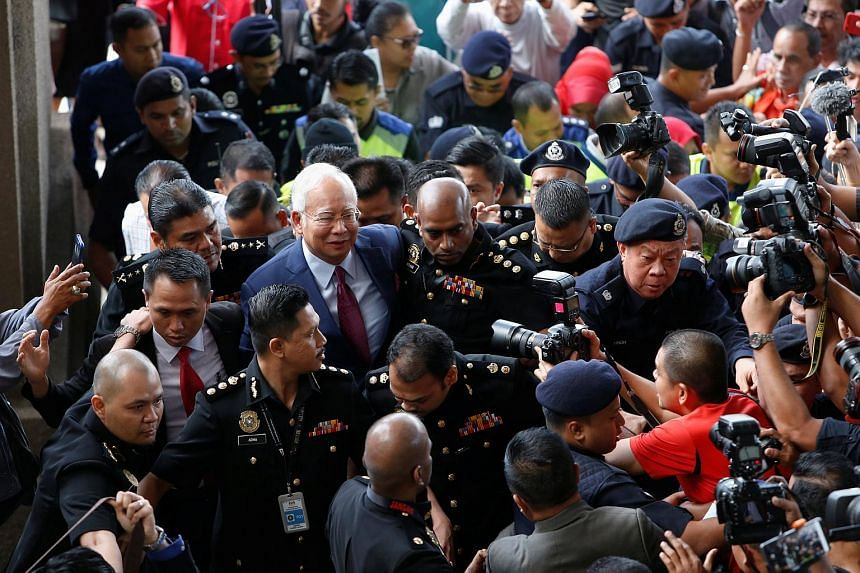Former Malaysian prime minister Najib Razak surrounded by police officers and members of the media as he arrives in court in Kuala Lumpur, Malaysia, on July 4, 2018.