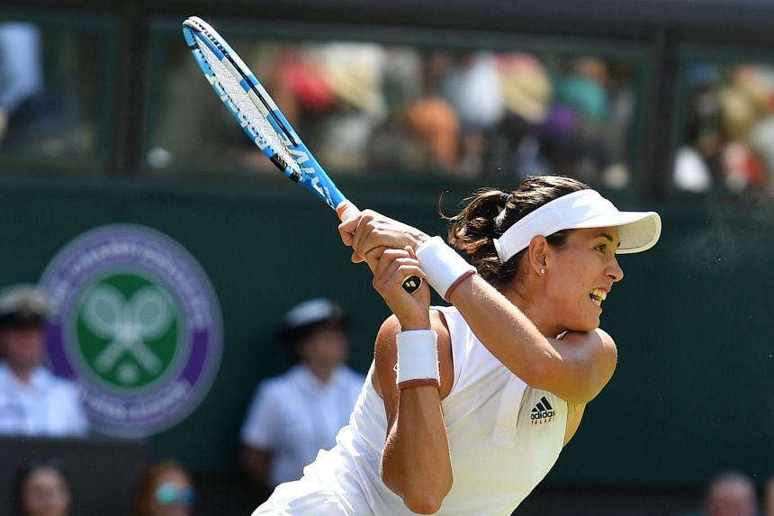 Spain's Garbine Muguruza hitting a return to Britain's Naomi Broady during their first-round match at The All England Lawn Tennis Club. The defending champion won in straight sets 6-2, 7-5.