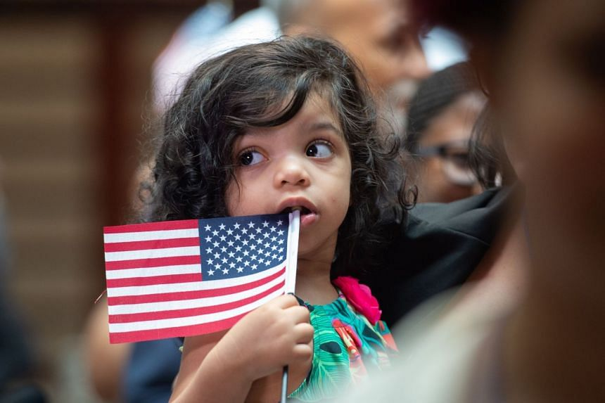 A little girl holds the flag as the US Citizenship and Immigration Services welcomes 200 new citizens from 50 countries during a ceremony in honour of Independence Day at the New York Public Library, July 3, 2018, in New York.