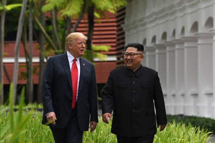 North Korea's leader Kim Jong Un (right) walks with US President Donald Trump during a break in talks at their historic US-North Korea summit, at the Capella Hotel on Sentosa island in Singapore on June 12, 2018.