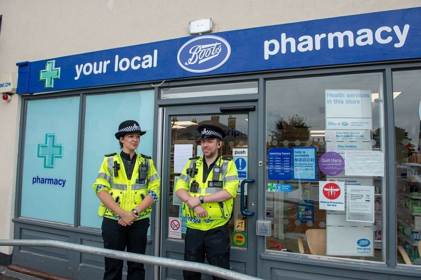 Police outside a Boots Pharmacy, which has been closed in relation to two people who were found unconscious.