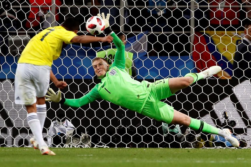 Left: Jordan Pickford gets his left hand to the ball, saving from the Colombian Carlos Bacca. It was the turning point in Tuesday's penalty shoot-out - and a moment of vindication for the 1.85m goalkeeper, who was labelled England's weak link by form