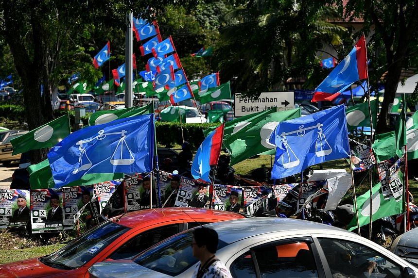 Rival political flags and banners outside a school in Pasir Gudang, Johor, on May 9. A vote for PAS, seen as the standard bearer of Islam, is a likely outcome if Umno is left severely weakened by the 1Malaysia Development Berhad investigations, says