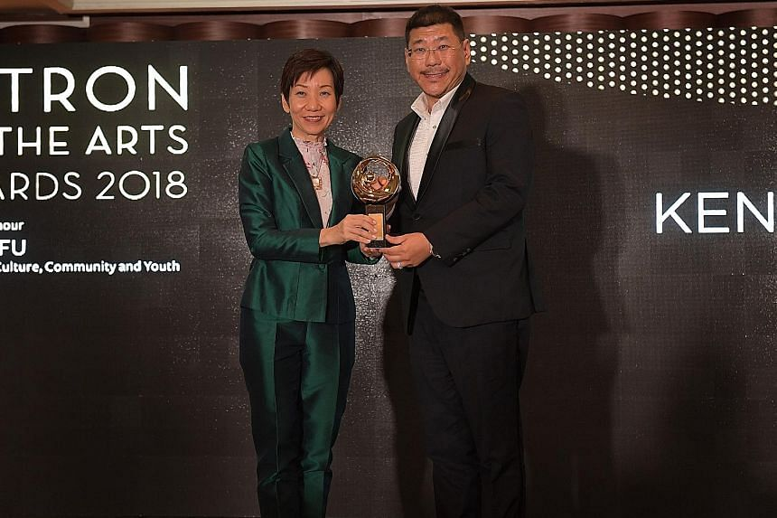 Mr Kenneth Kam, chairman of the Kenn Foundation, receiving the Distinguished Patron of the Arts award for individuals - who contribute $100,000 or more in a yearto the arts - from Minister for Culture, Community and Youth Grace Fu yesterday.