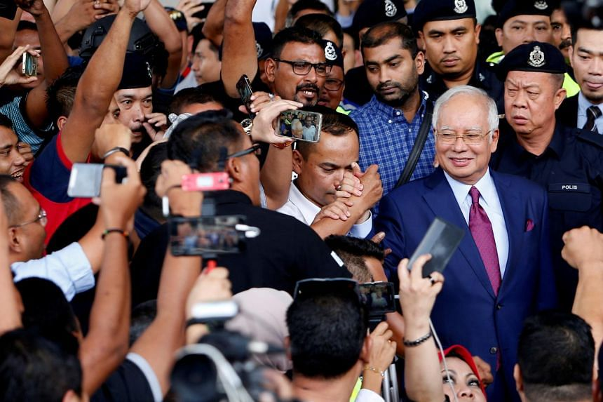 Malaysia's former prime minister Najib Razak greets his supporters as he leaves a court in Kuala Lumpur on July 4, 2018.