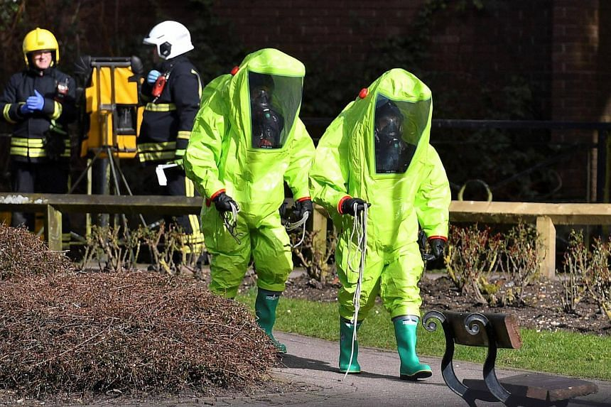 Members of the emergency services arrive to afix the tent over the bench where Sergei and Yulia Skripal were found in critical condition, in Salisbury, southern England, on March 8, 2018.