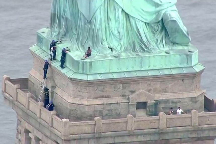 The protester started climbing the Statue of Liberty shortly after 3pm Eastern time on what was described as one of the busiest days of the year for the national monument in New York Harbor.