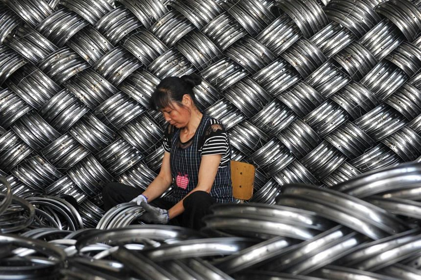 A worker checks wheel hubs of baby carriages that will be exported at a factory in Hangzhou in China's eastern Zhejiang province, on June 4, 2018.