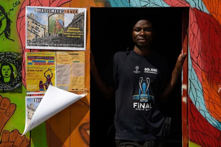 Ugandan Francis Kashamba poses at the front door of the abandoned school of La Massana, in the center of Barcelona, on July 3, 2018.
