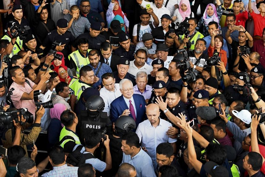 Former Malaysian prime minister Najib Razak (centre) is surrounded as he leaves the court complex after posting bail in Kuala Lumpur, on July 4, 2018.