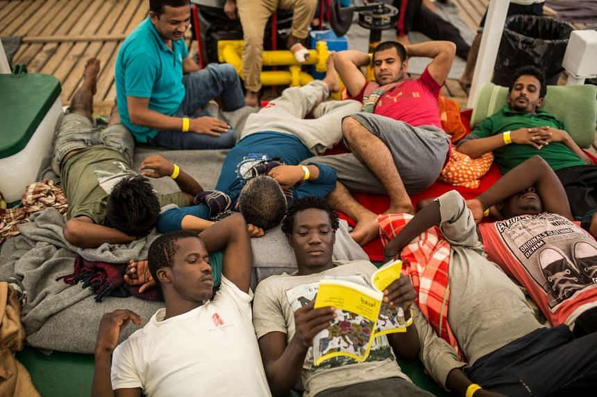 Rescued migrants rest on the deck of a boat belonging to the non-governmental organisation Proactiva Open Arms.