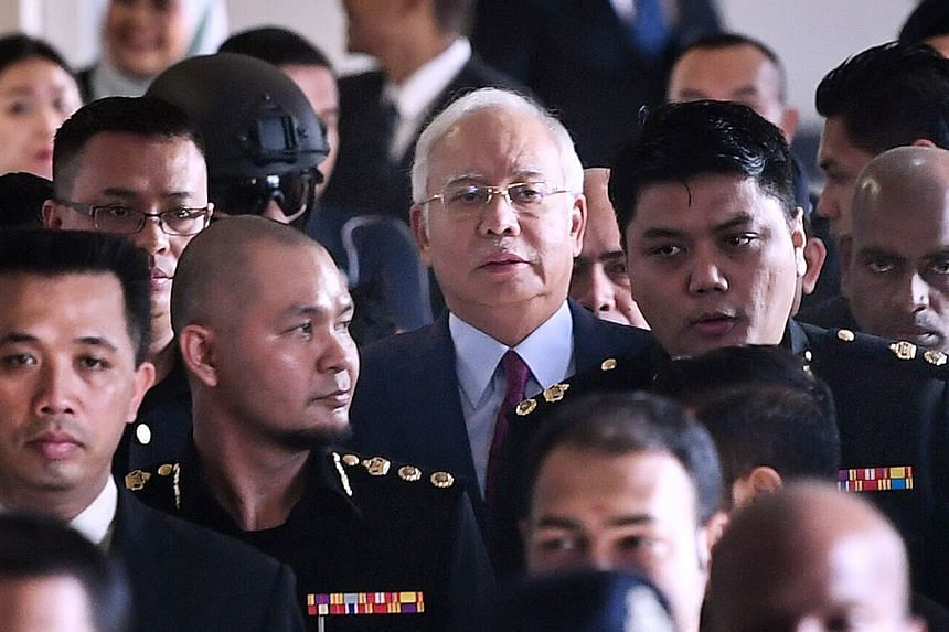 Former Malaysian prime minister Najib Razak under police escort after he was charged at the Kuala Lumpur High Court yesterday. His trial will take place in February and March next year.