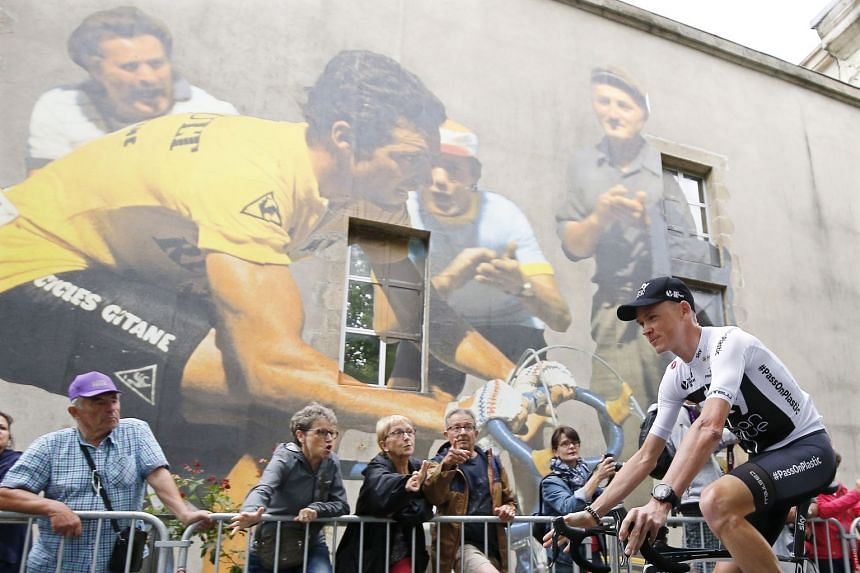 Froome passes by a mural depicting former French rider Bernard Hinault in La Roche-sur-Yon, France.