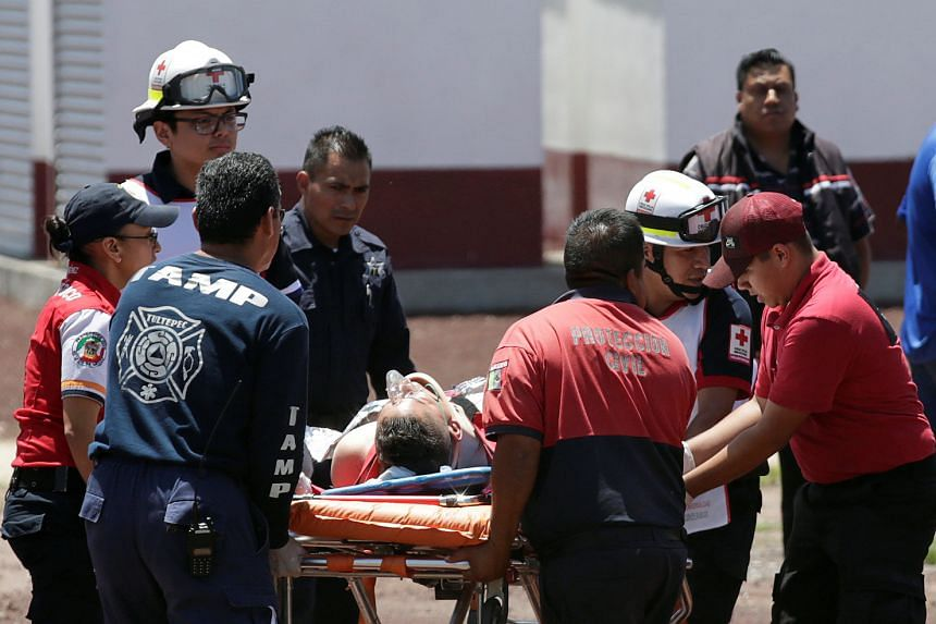 Paramedics wheel a stretcher carrying a man injured in the blasts.