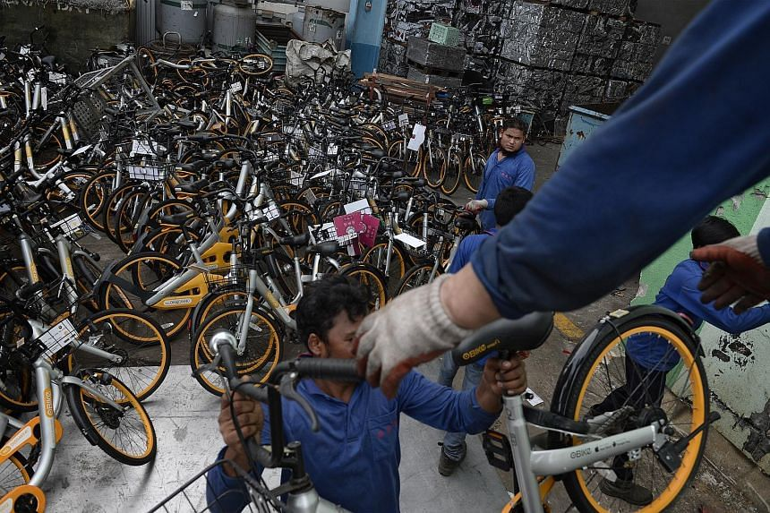 Employees of a recycling company unloading oBike two-wheelers meant for recycling from a lorry yesterday. As of Wednesday, the bike-sharing company had removed about 1,000 bicycles.