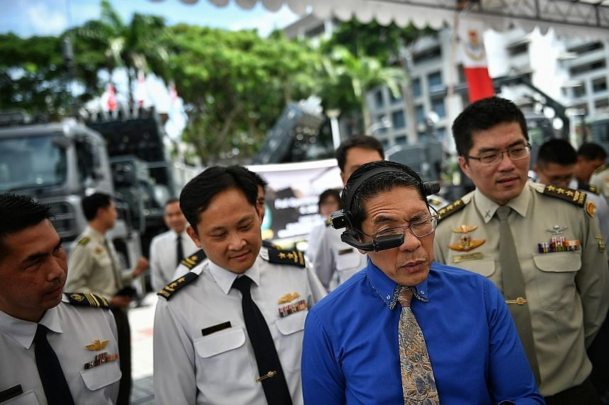 Senior Minister of State for Defence and Foreign Affairs Maliki Osman trying out the Spyder Remote Engineering Support smart glass. With him are Chief of Air Force Mervyn Tan (far left) and Chief of Defence Force Melvyn Ong. The Republic of Singapore